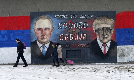 People walk by graffiti depicting the Russian President Vladimir Putin, left, and then-US President-elect Donald Trump, in Belgrade, Serbia, Jan. 20, 2017.
