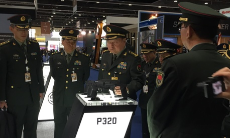 A Chinese military officer looks at a Sig Sauer handgun at the IDEX arms expo in Abu Dhabi in 2015.