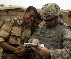 n this March 13, 2009 file photo, Iraqi Army soldiers look at a book of Arabic phrases as U.S. Army Staff Sgt. Robert Williams, 37, assigned to Delta Co., 1st Combined Arms Battalion, 67th Armor Regiment, looks for help in communicating in Mosul.