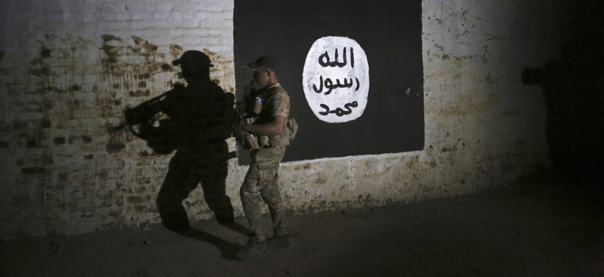 An Iraqi soldier inspects a recently-discovered train tunnel, adorned with an Islamic State group flag, that belonged to the former Baghdad to Mosul line, that was turned it to a training camp for IS fighters, in western Mosul, Iraq, March 1, 2017.