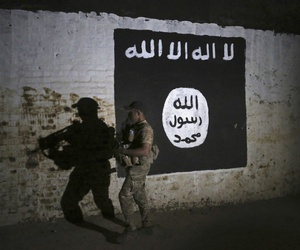 An Iraqi soldier inspects a recently-discovered train tunnel, adorned with an Islamic State group flag.