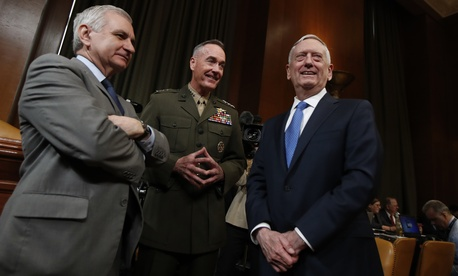 Joint Chiefs Chairman Gen. Joseph Dunford and Defense Secretary Jim Mattis confer with Sen. Jack Reed, D-R.I. (left), before testifying at the Senate Appropriations defense subcommittee.