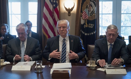 President Donald Trump is flanked on one side by Secretary of State Rex Tillerson, left, and on the other by Defense Secretary Jim Mattis.