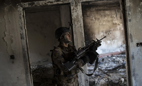 A Iraqi special forces soldier walks in a burned house near the front line during fighting against Islamic State militants in west Mosul, Iraq, Friday, March 17, 2017.