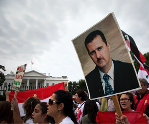 Protesters carry an image of Syrian President Bashar Hafez al-Assad during a demonstration against US military action in Syria, Monday, Sept. 9, 2013, in front of the White House in Washington.