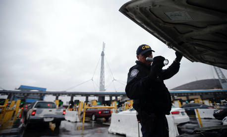 In this Dec. 3, 2014 file photo, a U.S. Customs and Border Protection (CBP) officer checks under the hood of a car as it waits to enter the U.S. from Tijuana, Mexico through the San Ysidro port of entry in San Diego.