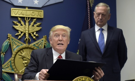 President Donald Trump, left, with Defense Secretary James Mattis, right, watching, explains the executive action on extreme vetting that he is about to sign at the Pentagon in Washington, January 27, 2017.