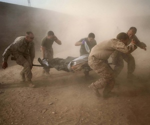 United States Marines run through dust kicked up by a Blackhawk helicopter as they rush a colleague wounded in an IED strike for evacuation near Sangin, Helmand Province, Afghanistan, on May 10, 2011.