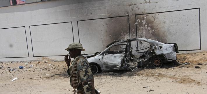A Somali soldier walks near the wreckage of a car bomb blast near Aden Abdule international airport in Mogadishu, Somalia, Sunday, April, 16, 2017.