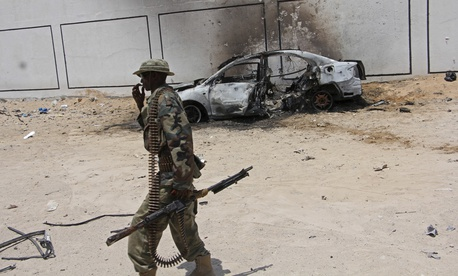A Somali soldier walks near the wreckage of a car bomb blast near Aden Abdule international airport in Mogadishu, Somalia, Sunday, April, 16, 2017.
