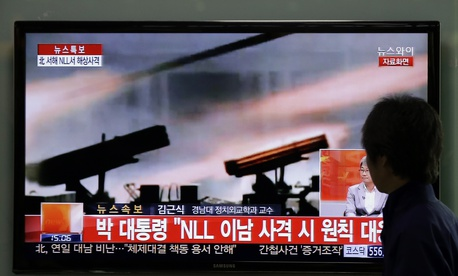 A man watches a television news program reporting about North Korea's live-fire artillery drills at a Seoul train station in Seoul, South Korea, Tuesday, April 29, 2014.