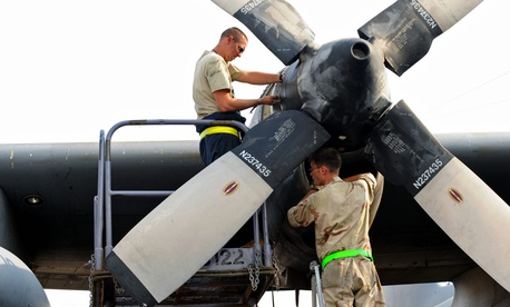 U.S. Air Force Tech. Sgt. Christopher Chadwell, left, performs a propeller hydraulic fluid level check while Staff Sgt. William Aker does an engine inlet inspection on a C-130E Hercules aircraft somewhere in southwest Asia on Aug.11, 2010.