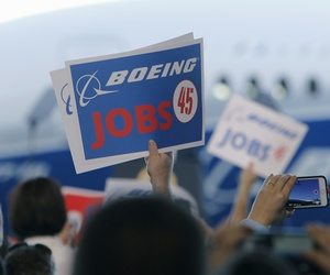 Boeing employees hold up signs as President Donald Trump speaks on Feb. 17, at company factory in North Charleston, S.C.