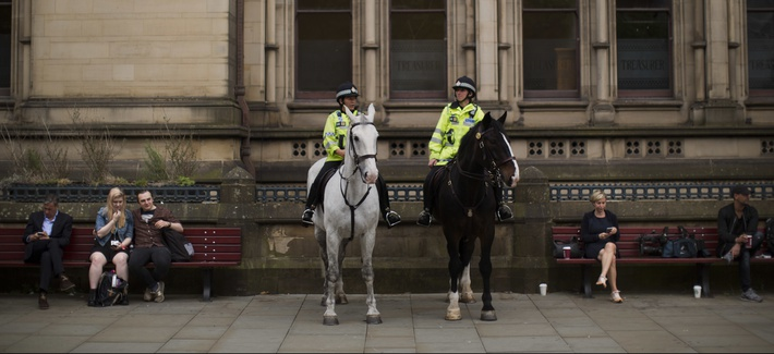Mounted police officers keep watch as people place flowers in Albert Square in Manchester, Britain, Wednesday, May 24, 2017.