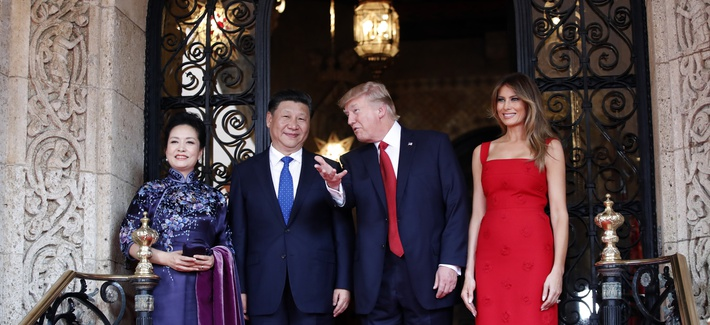 President Donald Trump talks with Chinese President Xi Jinping, with their wives, first lady Melania Trump and Chinese first lady Peng Liyuan as they pose for photographers before dinner at Mar-a-Lago, Thursday, April 6, 2017, in Palm Beach, Fla.