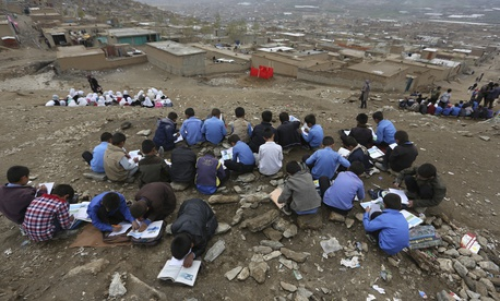 In this Wednesday, April 5, 2017, photo, Afghan students attend school classes an open air primary school on the outskirts of Kabul, Afghanistan.