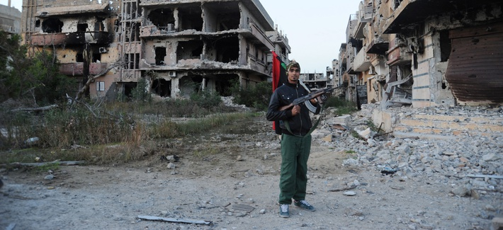 In this February 2016 photo, a civilian fighter holding the Libyan flag stands in front of damaged buildings in Benghazi, Libya.