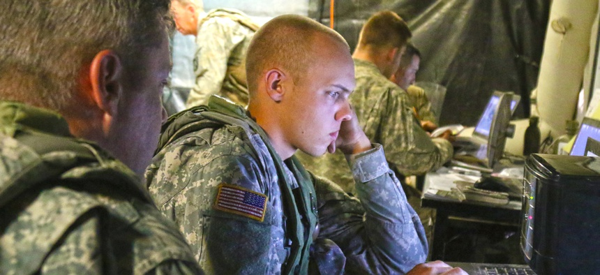 Spc. Clayton McInnis, a human intelligence analyst, with 1st Battalion, 155th Infantry Regiment, Mississippi Army National Guard, reviews reports in the unit's tactical operations center at the National Training Center.