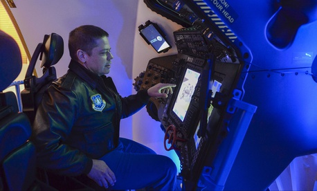 An astronaut from Air Force Space Command, pilots the Boeing Starliner simulator at the 33rd Space Symposium in Colorado Springs, Colo., April 6, 2017.