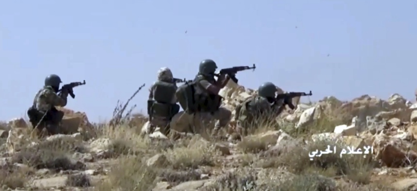 This frame grab from video released on Saturday, July 22, 2017 and provided by the government-controlled Syrian Central Military Media, shows Hezbollah fighters taking position during clashes with al-Qaida-linked militants in an area on the Lebanon-Syria