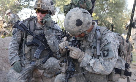 U.S. Army 1st Lt. Andrew Moehl of the 101st Airborne Division radios in his team's status with help from Spc. Joshua Rachal in Kandalay, Afghanistan, on Sept. 25, 2010.