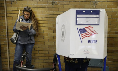Because all the privacy booths are full, Miriam Rodriguez fills out her ballot while leaning against the wall at a polling site in New York, Tuesday, Nov. 4, 2014.