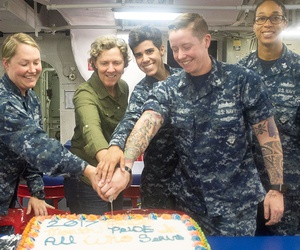 Command Master Chief (Ret.) Kathleen Henson, from Midland, Mich.,, center, and USS Makin Island Sailors cut a cake during the Lesbian, Gay, Bisexual, and Transgender Pride Month observance in June.