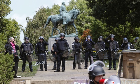 State Police in riot gear guard Lee Park after a white nationalist demonstration was declared illegal and the park was cleared in Charlottesville, Va., Saturday, Aug. 12, 2017.