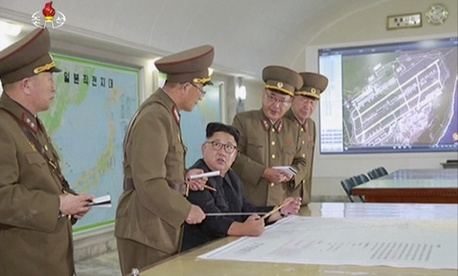 This image made from video of an Aug. 14, 2017, still image broadcast in a news bulletin on Tuesday, Aug. 15, 2017, by North Korea's KRT shows North Korean leader Kim Jong Un receiving a briefing in Pyongyang.