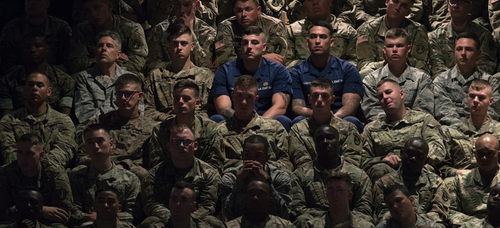 Members of the military in the audience look to President Donald Trump as he speaks at Fort Myer about his administration's policy for Afghanistan.