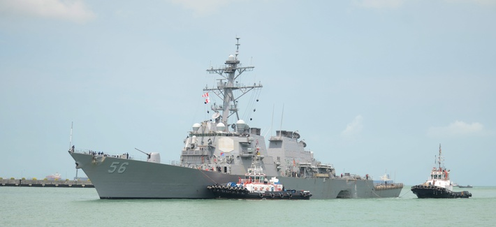 Tugboats from Singapore assist the Guided-missile destroyer USS John S. McCain as it steers towards Changi Naval Base, Republic of Singapore following a collision with the merchant vessel.