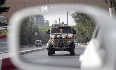 A patrolling U.S. armored vehicle is reflected in the mirror of a car in Kabul, Afghanistan, Wednesday, Aug. 23, 2017.