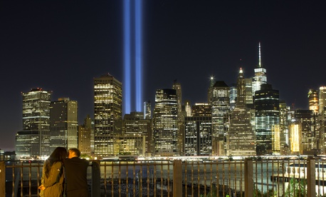 A couple embraces on the Brooklyn Promenade as the Tribute in Light rises above the lower Manhattan skyline Sunday, Sept. 10, 2017, in New York.