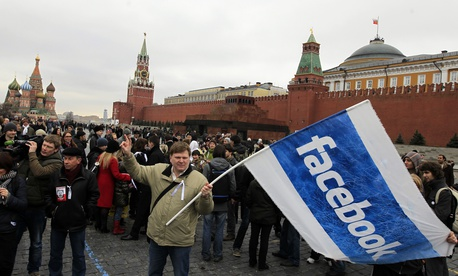 Opposition supporter waves a Facebook flag during a protest at the Red Square in Moscow, Sunday, April 8, 2012. Opposition activists called for supporters to walk around Red Square on Sunday wearing the white ribbons that have become a protest symbol.