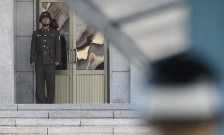 A North Korean soldier, left, looks at the South side as a South Korean soldier, right, stands guard at the truce village of Panmunjom in the Demilitarized Zone in Paju, South Korea, Sept. 28, 2017.