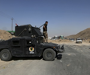 Federal security forces and local police stand guard in the northern entrance of Kirkuk while people return back to Kirkuk, 290 kilometers (180 miles) north of Baghdad, Iraq, Tuesday, Oct. 17, 2017.