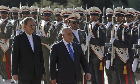 Iraqi Prime Minister Haider al-Abadi, center, reviews an honor guard while accompanied by Iranian Senior Vice-President Eshaq Jahangiri, at the Saadabad Palace in Tehran, Iran, Oct. 26, 2017.