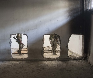 In this Oct. 20, 2017, photo, nembers of the U.S.-backed Syrian Democratic Forces (SDF) walk inside the stadium that was the site of Islamic State fighters' last stand in the city of Raqqa, Syria.