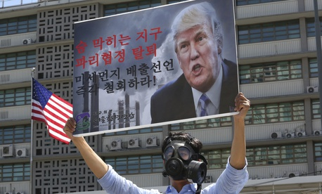 A South Korean environmental activist wearing a gas mask participates in a protest to denounce the U.S. withdrawal from the Paris climate accord, in front of the U.S. Embassy in Seoul, South Korea, Monday, June 5, 2017.