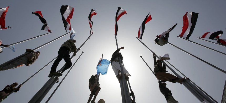 Supporters of Yemen's former President Ali Abdullah Saleh, who are allies of Shiite rebels knownas Houthis, climb flag poles during a rally to mark the first anniversary of the Saudi-led military campaign against them, in Sanaa, Yemen,March 26, 2016.