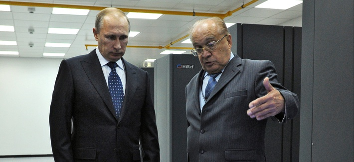 Russian President Vladimir Putin listens to an explanation of the head of Moscow's State University Viktor Sadovnichy, right, during a visit to laboratory, where super computer Lomonosov is placed, at the university on Thursday, Oct. 30, 2014