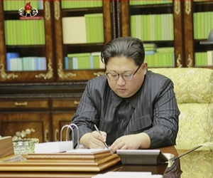 North Korea's leader Kim Jong Un signs what is said to be a document on Nov. 28, 2017, authorizing a missile test.