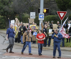 Anti-Muslim protestors cross the street as counter protestors look on in the background outside a mosque in Richardson, Texas, Dec. 12, 2015.