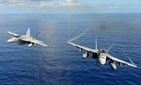 Two U.S. Navy F/A-18E Super Hornet participate in an air power demonstration in the Pacific Ocean on April 24, 2013.
