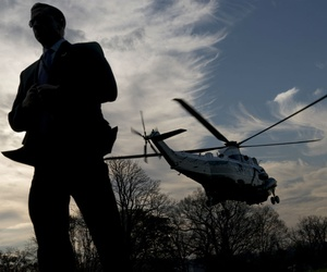A Secret Service Agent stands guard as Marine One leaves the White House. The House has passed a bill raising the overtime pay cap for agents.