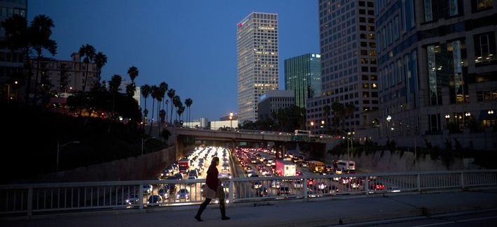 A woman walks on a bridge as heavy traffic moves along the 110 Freeway during rush hour Tuesday, Feb. 14, 2017, in Los Angeles.