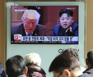 People watch a TV screen showing images of U.S. President Donald Trump, left, and North Korean leader Kim Jong Un at Seoul Railway Station in Seoul, South Korea, Nov. 21, 2017.