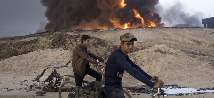 Iraqi youths ride bicycles next to a burning oil well in Qayara, about 31 miles (50 km) south of Mosul, Iraq, October 23, 2016.