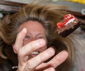 NASA astronaut Karen Nyberg floats a piece of food during mealtime. NASA astronaut Karen Nyberg floats a piece of food during mealtime.