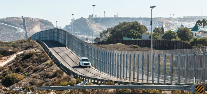 San Diego, California and Tijuana, Mexico international border wall with border patrol vehicle.